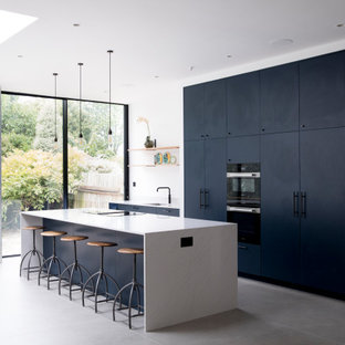 This is an example of an expansive contemporary galley open plan kitchen in London with an integrated sink, flat-panel cabinets, blue cabinets, quartz worktops, cement flooring, an island, grey floors, white worktops, white splashback and integrated appliances.