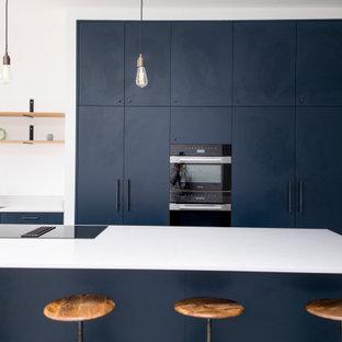Diseño de cocina de galera, minimalista, extra grande, abierta, con fregadero integrado, armarios con paneles lisos, puertas de armario azules, encimera de cuarcita, suelo de azulejos de cemento, una isla, suelo gris y encimeras blancas