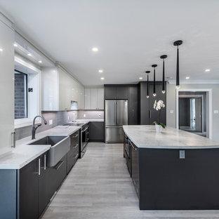 トロントの大きいモダンスタイルのおしゃれなキッチン (エプロンフロントシンク、フラットパネル扉のキャビネット、白いキャビネット、珪岩カウンター、グレーのキッチンパネル、サブウェイタイルのキッチンパネル、シルバーの調理設備の、クッションフロア、グレーの床、白いキッチンカウンター) の写真