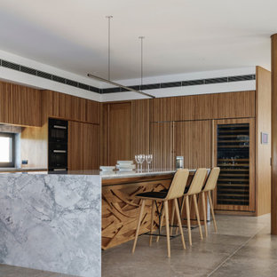 Photo of a contemporary u-shaped kitchen in Sydney with raised-panel cabinets, medium wood cabinets, marble benchtops, window splashback, panelled appliances, concrete floors, with island, grey floor and grey benchtop.
