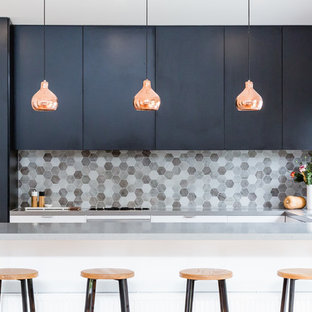 Inspiration for a contemporary u-shaped kitchen in Melbourne with a submerged sink, flat-panel cabinets, black cabinets, grey splashback, mosaic tiled splashback and a breakfast bar.