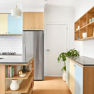 Large scandinavian kitchen pantry photos - Example of a large danish galley cork floor kitchen pantry design in Melbourne with a drop-in sink, beaded inset cabinets, medium tone wood cabinets, concrete countertops, white backsplash, subway tile backsplash, stainless steel appliances and an island