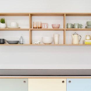 Immagine di una grande cucina scandinava con lavello da incasso, ante a filo, ante in legno scuro, top in cemento, paraspruzzi bianco, paraspruzzi con piastrelle diamantate, elettrodomestici in acciaio inossidabile, pavimento in sughero e isola