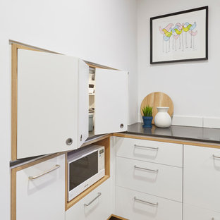 Photo of a large scandinavian galley kitchen pantry in Melbourne with a drop-in sink, beaded inset cabinets, medium wood cabinets, concrete benchtops, white splashback, subway tile splashback, stainless steel appliances, cork floors and with island.
