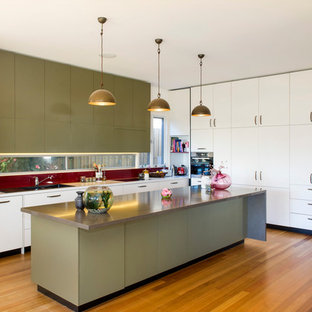 Photo of a large transitional l-shaped open plan kitchen in Melbourne with flat-panel cabinets, green cabinets, red splashback, light hardwood floors, with island, a double-bowl sink, quartz benchtops, glass sheet splashback, stainless steel appliances, brown floor and brown benchtop.