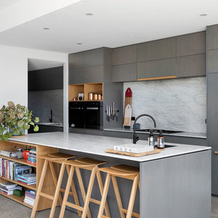 Mid-sized contemporary galley kitchen in Melbourne with flat-panel cabinets, marble benchtops, marble splashback, black appliances, concrete floors, with island, grey floor, an undermount sink, grey cabinets, white splashback and white benchtop.
