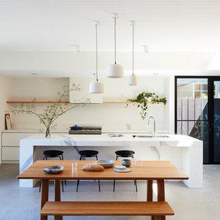メルボルンの大きいコンテンポラリースタイルのおしゃれなキッチン (アンダーカウンターシンク、白いキッチンパネル、レンガのキッチンパネル、シルバーの調理設備の、コンクリートの床、グレーの床、白いキッチンカウンター、フラットパネル扉のキャビネット、白いキャビネット) の写真