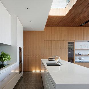 Modelo de cocina comedor de galera, contemporánea, de tamaño medio, con puertas de armario blancas, suelo de cemento, una isla, salpicadero negro, salpicadero de azulejos de piedra y fregadero bajoencimera