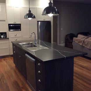 メルボルンの中サイズのヴィクトリアン調のおしゃれなキッチン (ダブルシンク、落し込みパネル扉のキャビネット、中間色木目調キャビネット、クオーツストーンカウンター、黒いキッチンパネル、セラミックタイルのキッチンパネル、シルバーの調理設備、無垢フローリング) の写真