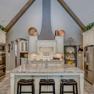 Klassisk inredning av ett stort kök, med en rustik diskho, luckor med upphöjd panel, granitbänkskiva, stänkskydd i porslinskakel, rostfria vitvaror, klinkergolv i porslin, en köksö, beige skåp, beige stänkskydd och beiget golv