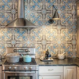 Foto di una cucina chic con ante con bugna sagomata, elettrodomestici in acciaio inossidabile, top in saponaria e paraspruzzi blu