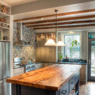 Foto de cocina en L, tradicional, con armarios con paneles con relieve, encimera de madera, puertas de armario azules, salpicadero azul y electrodomésticos de acero inoxidable