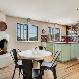 他の地域の中サイズのサンタフェスタイルのおしゃれなキッチン (ダブルシンク、シェーカースタイル扉のキャビネット、緑のキャビネット、マルチカラーのキッチンパネル、サブウェイタイルのキッチンパネル、シルバーの調理設備の、淡色無垢フローリング、ベージュの床) の写真