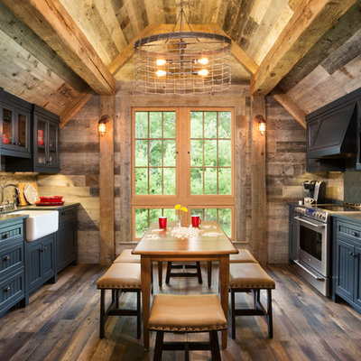 Mountain style galley medium tone wood floor and brown floor eat-in kitchen photo in Minneapolis with a farmhouse sink, quartzite countertops, paneled appliances, shaker cabinets, black cabinets and no island