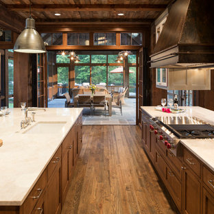 Rustic eat-in kitchen designs - Inspiration for a rustic u-shaped medium tone wood floor eat-in kitchen remodel in Minneapolis with granite countertops, paneled appliances and two islands