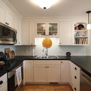 ミネアポリスの小さいカントリー風おしゃれなキッチン (ドロップインシンク、シェーカースタイル扉のキャビネット、白いキャビネット、ラミネートカウンター、白いキッチンパネル、セラミックタイルのキッチンパネル、シルバーの調理設備の、淡色無垢フローリング) の写真
