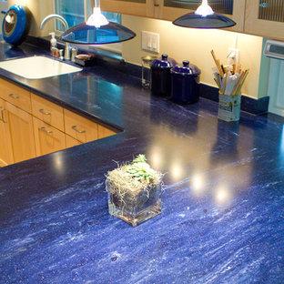 Diseño de cocina en L, ecléctica, de tamaño medio, abierta, con fregadero de un seno, armarios estilo shaker, puertas de armario de madera clara, encimera de acrílico, salpicadero azul, electrodomésticos de acero inoxidable, suelo de madera clara, una isla y encimeras azules