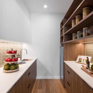 Large contemporary galley kitchen pantry in Brisbane with medium wood cabinets, quartz benchtops, ceramic splashback, white benchtop, an undermount sink, flat-panel cabinets, grey splashback, medium hardwood floors, no island and brown floor.