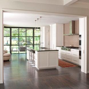 Cette image montre une cuisine ouverte parallèle traditionnelle avec un évier encastré, un placard à porte shaker, des portes de placard blanches, une crédence beige et un électroménager en acier inoxydable.