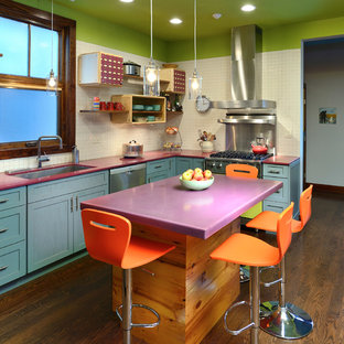 Modelo de cocina en L, ecléctica, con fregadero bajoencimera, armarios estilo shaker, puertas de armario azules, salpicadero blanco, electrodomésticos de acero inoxidable, suelo de madera oscura, una isla y encimeras moradas