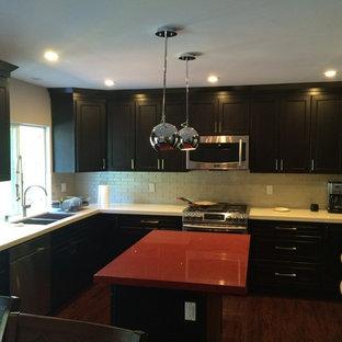 ロサンゼルスの大きいサンタフェスタイルのおしゃれなキッチン (ダブルシンク、フラットパネル扉のキャビネット、濃色木目調キャビネット、御影石カウンター、ベージュキッチンパネル、サブウェイタイルのキッチンパネル、シルバーの調理設備の、濃色無垢フローリング) の写真