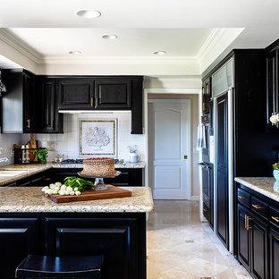Ispirazione per una cucina classica di medie dimensioni con lavello sottopiano, ante con bugna sagomata, ante nere, top in granito, paraspruzzi bianco, paraspruzzi con piastrelle in ceramica, elettrodomestici in acciaio inossidabile, pavimento in travertino, pavimento beige e top beige