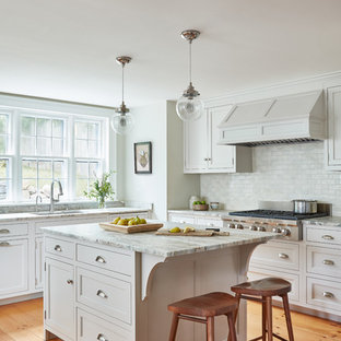 Classic l-shaped kitchen in Boston with a submerged sink, shaker cabinets, white cabinets, white splashback, medium hardwood flooring, an island and brown floors.