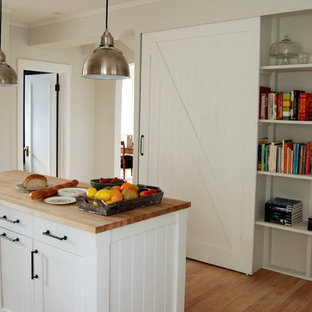 Example of a cottage kitchen design in Chicago with wood countertops, open cabinets and white cabinets