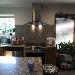 オースティンの中くらいのエクレクティックスタイルのおしゃれなキッチン (アンダーカウンターシンク、ガラス扉のキャビネット、中間色木目調キャビネット、珪岩カウンター、グレーのキッチンパネル、セラミックタイルのキッチンパネル、シルバーの調理設備、セラミックタイルの床、ベージュの床、グレーのキッチンカウンター) の写真