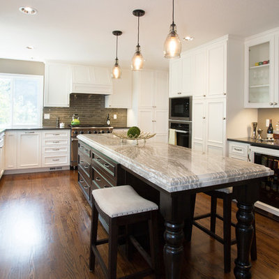 Example of a large classic u-shaped medium tone wood floor open concept kitchen design in Portland with an undermount sink, beaded inset cabinets, white cabinets, quartz countertops, beige backsplash, glass tile backsplash, stainless steel appliances, an island and black countertops