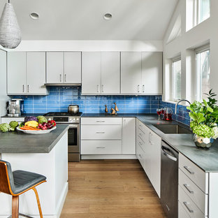 Inspiration for a large midcentury l-shaped kitchen in Austin with flat-panel cabinets, grey cabinets, quartz benchtops, blue splashback, glass tile splashback, stainless steel appliances, light hardwood floors, with island, grey benchtop, a single-bowl sink and beige floor.