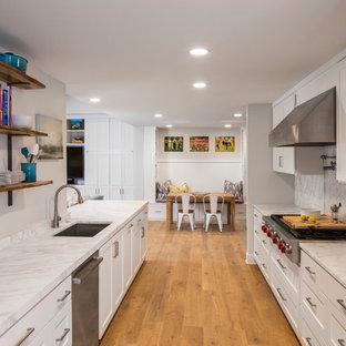 オースティンの中サイズのエクレクティックスタイルのおしゃれなキッチン (シングルシンク、シェーカースタイル扉のキャビネット、白いキャビネット、大理石カウンター、白いキッチンパネル、淡色無垢フローリング、アイランドなし) の写真