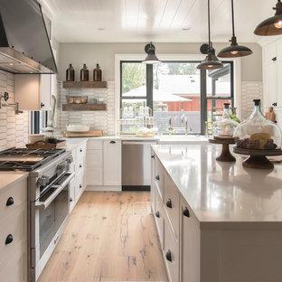 Exemple d'une cuisine nature en U avec un évier de ferme, un placard à porte shaker, des portes de placard blanches, une crédence blanche, un électroménager en acier inoxydable, un sol en bois brun, un îlot central, un sol marron et un plan de travail blanc.