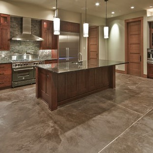Huge trendy u-shaped concrete floor eat-in kitchen photo in Seattle with a farmhouse sink, recessed-panel cabinets, medium tone wood cabinets, granite countertops, brown backsplash, stone tile backsplash, stainless steel appliances and an island