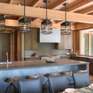 他の地域のラスティックスタイルのおしゃれなキッチン (エプロンフロントシンク、フラットパネル扉のキャビネット、濃色木目調キャビネット、ライムストーンカウンター、グレーのキッチンパネル、シルバーの調理設備、ガラスまたは窓のキッチンパネル) の写真
