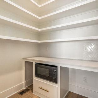 Einzeilige Moderne Küche mit Vorratsschrank, integriertem Waschbecken, weißen Schränken, Küchenrückwand in Weiß, Rückwand aus Keramikfliesen, Küchengeräten aus Edelstahl, braunem Holzboden, Kücheninsel, braunem Boden, weißer Arbeitsplatte und freigelegten Dachbalken in Louisville