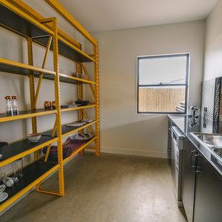 ケアンズのインダストリアルスタイルのおしゃれなI型キッチン (ダブルシンク、オープンシェルフ、黄色いキャビネット、ステンレスカウンター、アイランドなし、茶色い床、グレーのキッチンカウンター) の写真