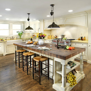 Design ideas for a traditional kitchen in Chicago with stainless steel appliances, a belfast sink, wood worktops and yellow worktops.