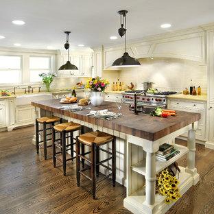 Пример оригинального дизайна: кухня в классическом стиле с техникой из нержавеющей стали, раковиной в стиле кантри, деревянной столешницей и желтой столешницей