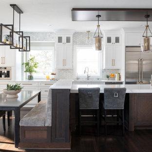 ミネアポリスの広いトランジショナルスタイルのおしゃれなキッチン (落し込みパネル扉のキャビネット、白いキャビネット、クオーツストーンカウンター、グレーのキッチンパネル、大理石のキッチンパネル、シルバーの調理設備、白いキッチンカウンター、トリプルシンク、無垢フローリング、茶色い床、板張り天井) の写真