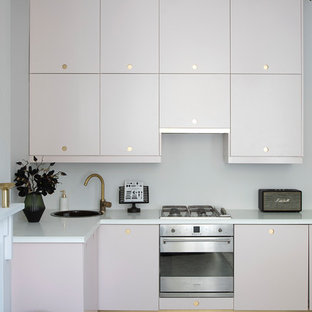 This is an example of a contemporary l-shaped kitchen in London with a drop-in sink, flat-panel cabinets, purple cabinets, white splashback, stainless steel appliances, grey floor and white benchtop.