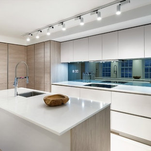 This is an example of a large contemporary l-shaped kitchen/diner in London with a submerged sink, flat-panel cabinets, white cabinets, mirror splashback, black appliances, an island, beige floors, white worktops, composite countertops, metallic splashback and limestone flooring.