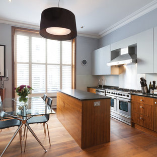 Inspiration for a medium sized contemporary galley kitchen/diner in London with flat-panel cabinets, medium wood cabinets, stainless steel appliances, medium hardwood flooring, an island, a built-in sink, granite worktops, blue splashback, glass sheet splashback, brown floors and black worktops.
