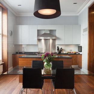ロンドンの広いエクレクティックスタイルのおしゃれなキッチン (ドロップインシンク、フラットパネル扉のキャビネット、淡色木目調キャビネット、御影石カウンター、青いキッチンパネル、ガラス板のキッチンパネル、パネルと同色の調理設備、無垢フローリング、茶色い床、黒いキッチンカウンター) の写真