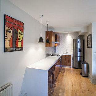 Inspiration for a contemporary l-shaped enclosed kitchen remodel in London with an undermount sink, flat-panel cabinets, white backsplash, stainless steel appliances, subway tile backsplash, medium tone wood cabinets and white countertops