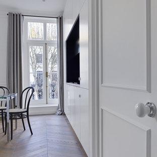 ロンドンの小さいヴィクトリアン調のおしゃれなキッチン (ドロップインシンク、落し込みパネル扉のキャビネット、白いキャビネット、木材カウンター、黒いキッチンパネル、黒い調理設備、淡色無垢フローリング、アイランドなし、茶色い床、黒いキッチンカウンター) の写真