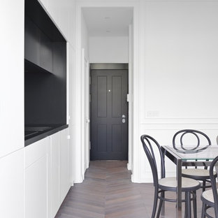 Design ideas for a small traditional single-wall open plan kitchen in London with a drop-in sink, recessed-panel cabinets, white cabinets, wood benchtops, black splashback, black appliances, light hardwood floors, no island, brown floor and black benchtop.