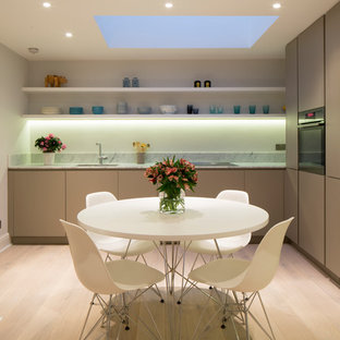 This is an example of a small modern l-shaped open plan kitchen in London with flat-panel cabinets, beige cabinets, marble worktops, light hardwood flooring, no island and white worktops.