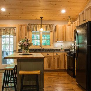 На фото: кухни в стиле кантри с фасадами в стиле шейкер, врезной раковиной, фасадами цвета дерева среднего тона, столешницей из кварцевого агломерата, черной техникой, паркетным полом среднего тона и островом
