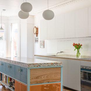 Moderne Wohnküche mit Arbeitsplatte aus Terrazzo, braunem Holzboden, Kücheninsel, braunem Boden und grauer Arbeitsplatte in London